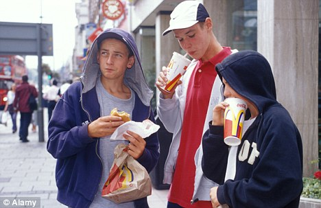 Teenage boys in hoods eating junk food in the streets
