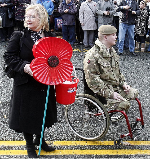 Helping the injured: Julie Dove from the Poppy Appeal attends an Armistice Day service at Chester Cathedral with a members of the 1st Battalion the Mercians who lost his legs in combat