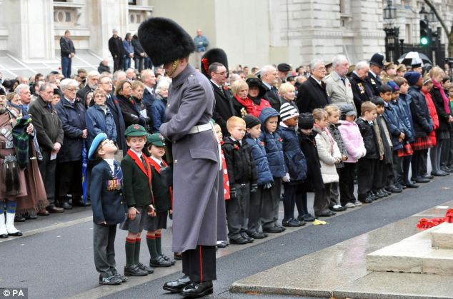 Looking up: Seven-year-old Jonny Osborne, wearing his great great uncle's medals, comes face-to-face with a soldier at the ceremony