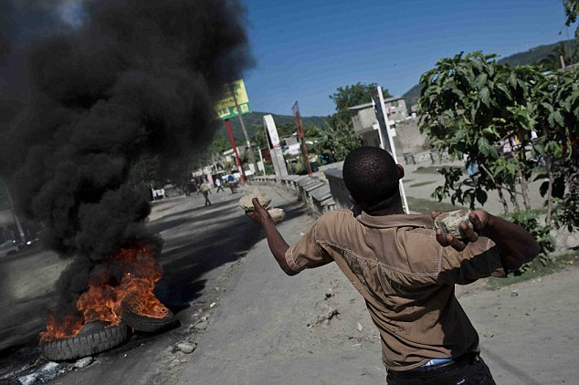 Riots: Locals in Haiti's second city Cap Haitien throw stones at UN peacekeepers who they blame for brining cholera to the country