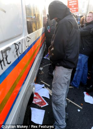 Light relief: A demonstrator urinates against a police van