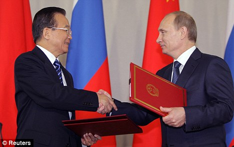 Moving forward: Russia's Prime Minister Vladimir Putin and China's Premier Wen Jiabao exchange documents during their meeting in St Petersburg on Tuesday