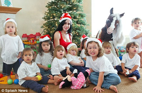 Nadya Suleman aka 'Octomom' shot pictures for her family Christmas card today. All eight toddlers who are now nearly 2 years old were in the picture including a couple older kids. The picture was taken in front of a lighted tree in her living room.