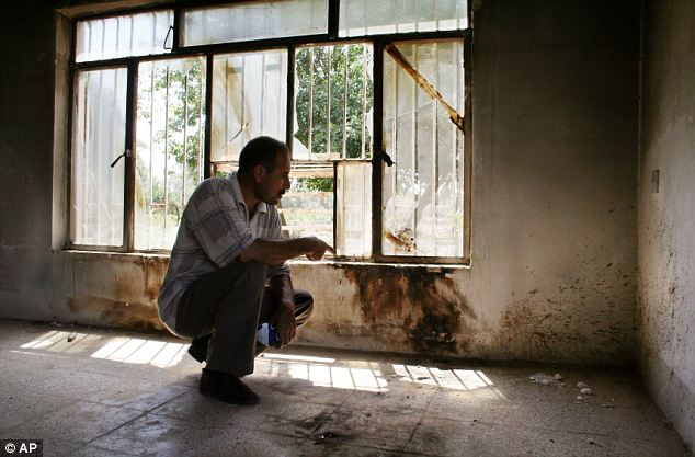 Neighbour Hussein Mohammed points to the charred and blood-splattered crime scene where the killings took place in Mahmoudiya, Iraq