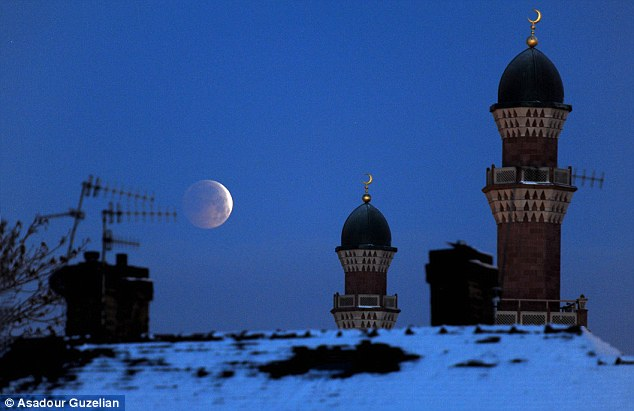 The winter solstice lunar eclipse as seen over rooftops and Horton Park mosque, Bradford