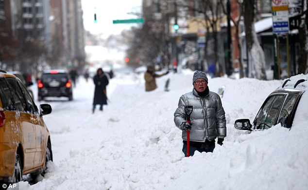 A man tried to dig his car out on 72nd Street in New York after the blizzard buried it