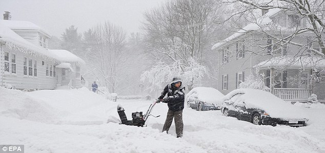 Hard work: A resident clears the end of his driveway with a snowblower along Route 1A in Walpole, Massachusetts