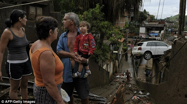 Taking stock: A family looks around their destroyed house in an area affected by a mudslide and where they believe dozens of victims are still buried, at Morro do Dede neighbourhood in Nova Friburgo
