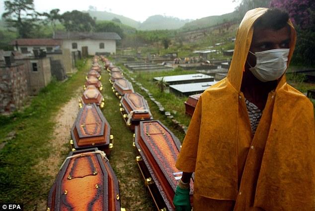 Burial: A man stands near coffins of victims of the catastrophe at the Trilha do Ceu graveyard, Conselheiro Paulino district, Nova Friburgo