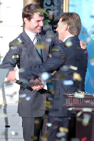 Confetti rains down as U.S. actor Tom Cruise, left, embraces David Miscavige, the Scienology Church's President of the Rulling Council during the official opening of a new Scientology church in central Madrid in this Sept. 18, 2004