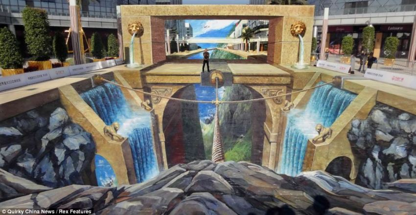 Creative: Artist Qi Xinghua proudly stands on his huge 3D painting at the Guangzhou Baiyan Wanda Plaza in Guangzhou, China. His work has officially been recognised as the world's largest 3D picture