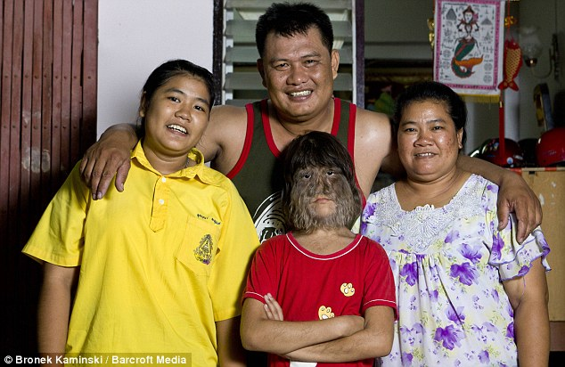 Happily families: Suptara with her sister 15-year-old Sukanya, left, her father Sammrueng and mother Somphon