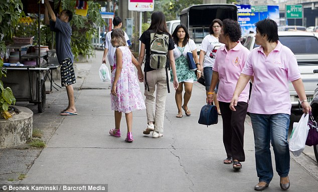 People in a street turn and stare as Supatra walks by in Bangkok, Thailand.