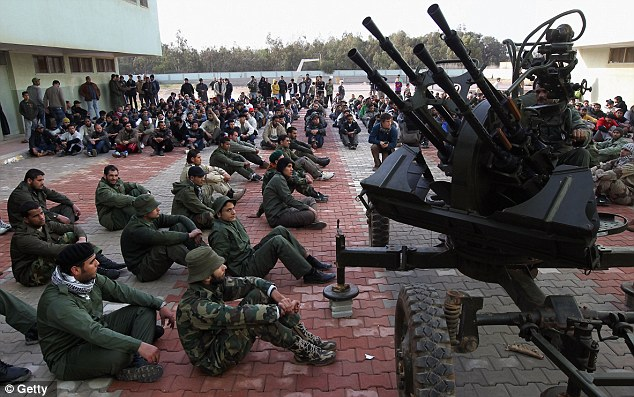 Opposition forces receive training today in the fight against Colonel Gaddafi. It comes as the British government was forced into an embarrassing retreat over its military plans for Libya