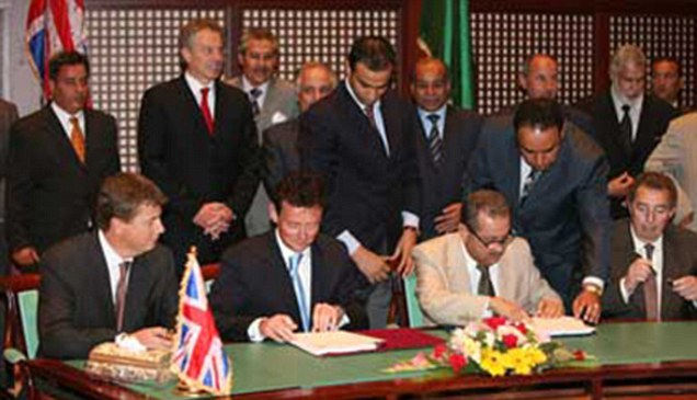 Tony Blair (stood to the left) with BP securing oil contract in Libya.