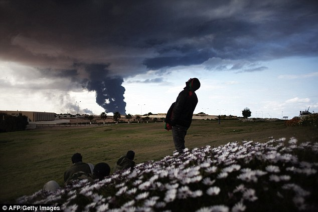 Plumes: Libyan rebels look at a smoke rising from an oil pipe just outside the town of Ras Lanuf