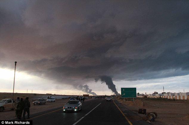 Gloomy: Smoke from burning oil fields in Ras Lanuf engulfs the sky