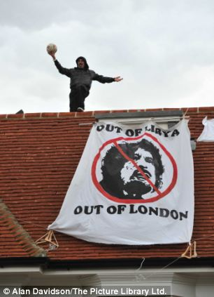 Rooftop protest: One of the protesters holds a football aloft as he stands by the banner demanding Gaddafi and his assets should get out of London