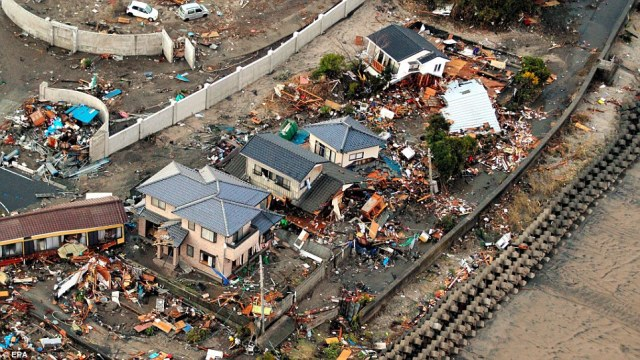 Destroyed: The remains of houses are surrounded by broken wood and concrete after flood waters engulfed Iwaki town, Fukushima prefecture