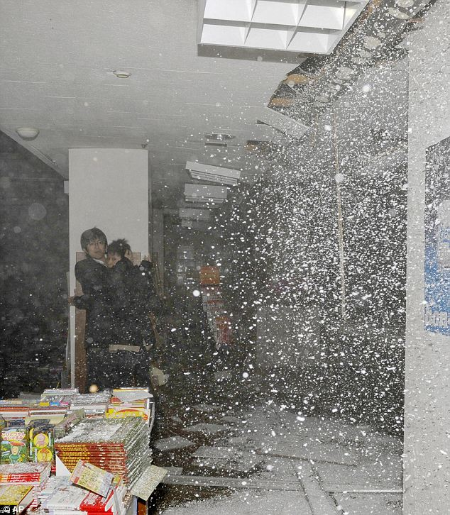 Moment of impact: People at a book store react as the store's ceiling falls in Sendai