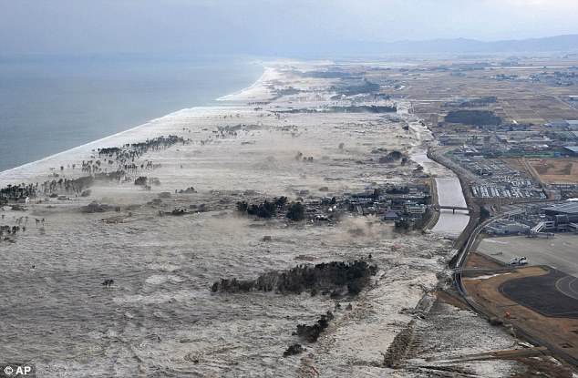 Terrifying: The tsunami slams into the shore line along Iwanuma in northern Japan after the 8.9 eathquake struck today