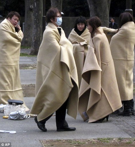 Stranded commuters wrap themselves in blankets bracing for chilly evening at a park in Yokohama, near Tokyo, following a strong earthquake hit eastern Japan on Friday, March 11,