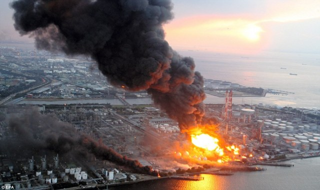 Aftermath: Clouds of grey smoke billow out of an oil refinery, and an inferno burns at its centre, in Chiba following the earthquake
