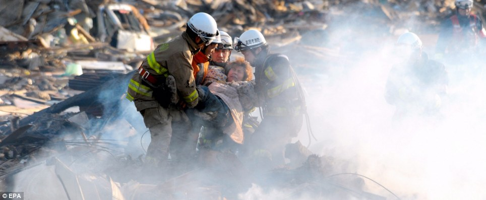 Alive: A woman is pulled from the rubble in the devastated city of Natori, Miyagi prefecture today