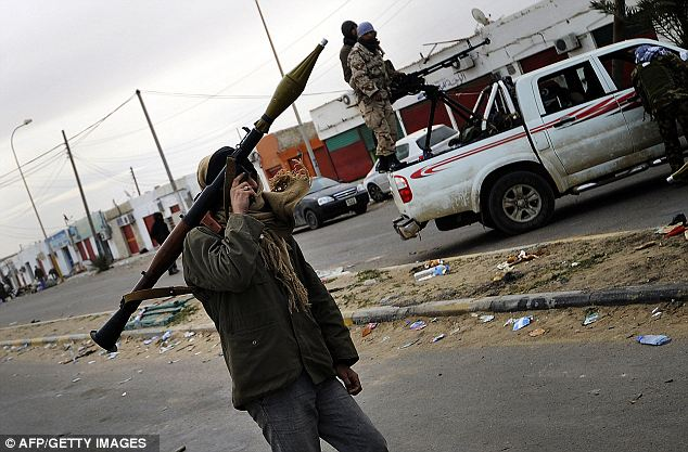 A Libyan rebel carries a rocket-propelled grenade launcher today before dozens of opposition fighters reportedly pulled out of the eastern town of Brega amid heavy shelling from forces loyal to strongman Gaddafi