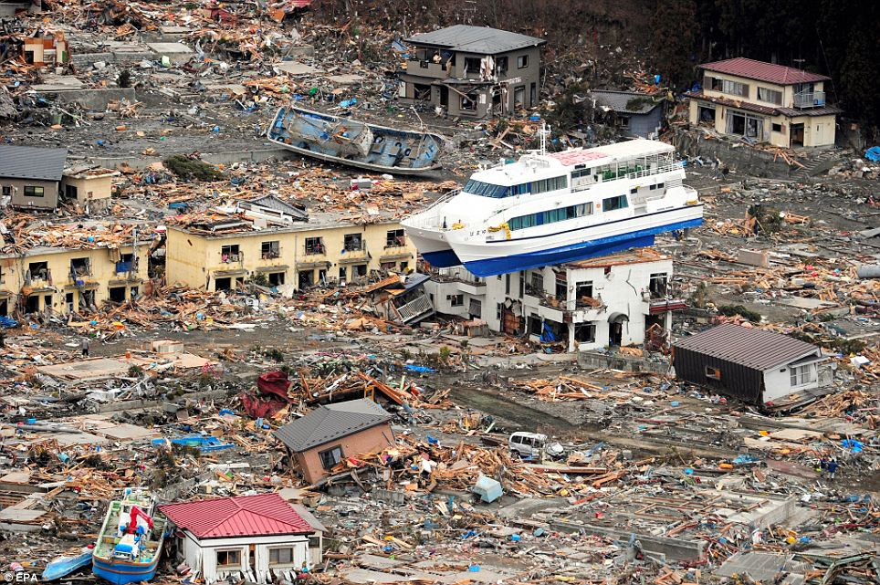 A ship is seen perched on top of a house in the tsunami devastated remains of Otsuchi, Iwate prefecture