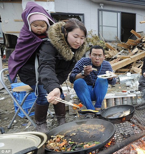 Tsunami survivors cook and eat in front of their damaged house Tuesday, March 15, 2011 in Ishinomaki in Miyagi Prefecture