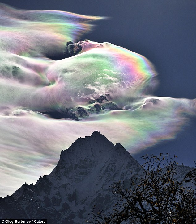 Dazzling: A rainbow cloud dwarfs Mount Everest in the Himalayas, taking photographer Oleg Bartunov by surprise