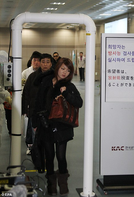 Tourists from Japan pass through a scanner checking radiation levels at the international ferry terminal in South Korea's southeastern port city of Busan