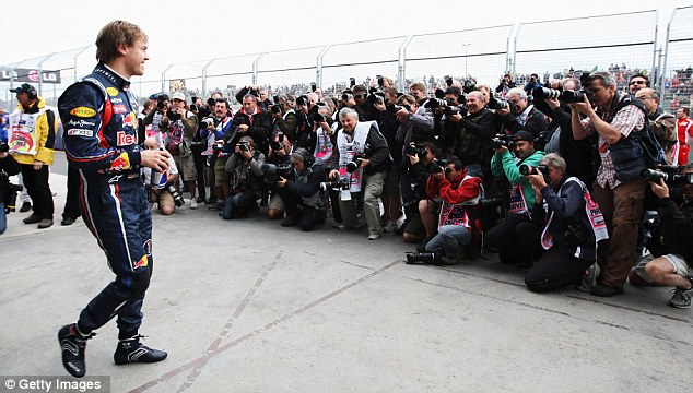 Smile, you're on camera: Sebastian Vettel meets the photographers in parc ferme after taking pole position
