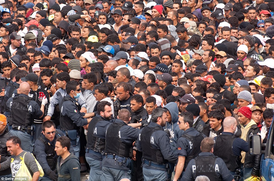 Sea of humanity: Italian police push back immigrants from Tunisia as they wait at the port for food in Lampedusa