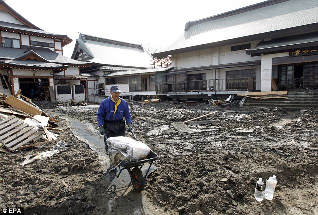 Little by little: A man helps clear rubbish and mud from a Buddhist temple in Ishinomaki