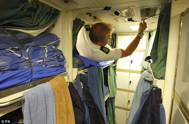 A crew member climbs into a bunk