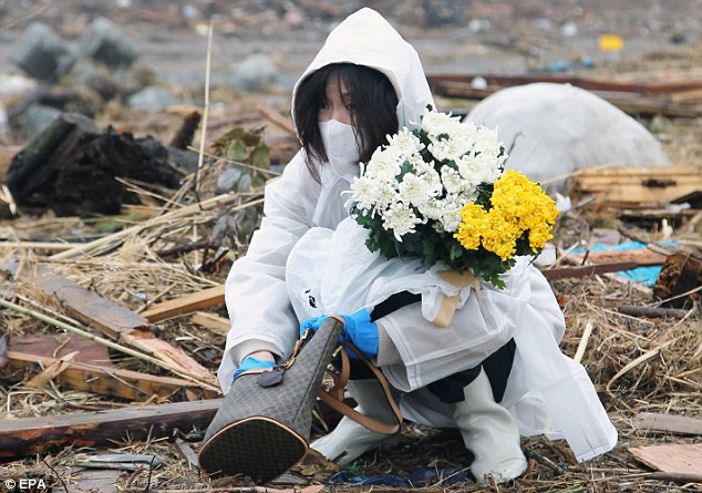 Prayers: A woman lays flowers where her house was swept away in Minamisoma