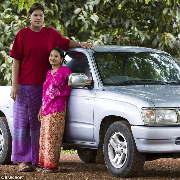 Malee Duangdee stands tall above a pick up truck and her friend, A Khoson
