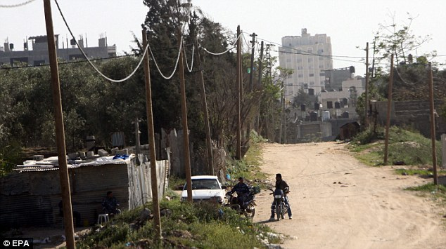 Abandoned: Hamas officials guard the house in the Al Karama area of Gaza City where Mr Arrigoni's body was found