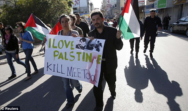 Kill me too: Palestinians and foreign activists carry banners through Ramallah after they heard of Arrigoni's murder