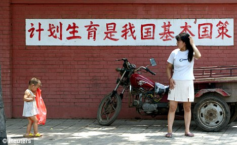 Controversial: A woman and her child walk by a birth control propaganda poster in China, which has a one-child policy