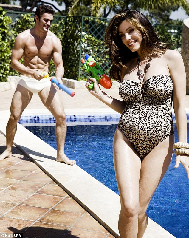 Blooming: Kelly Brook shows off her pregnancy curves in a leopard-print swimsuit while her incredibly muscular boyfriend Thom Evans larks around in the background with a water gun