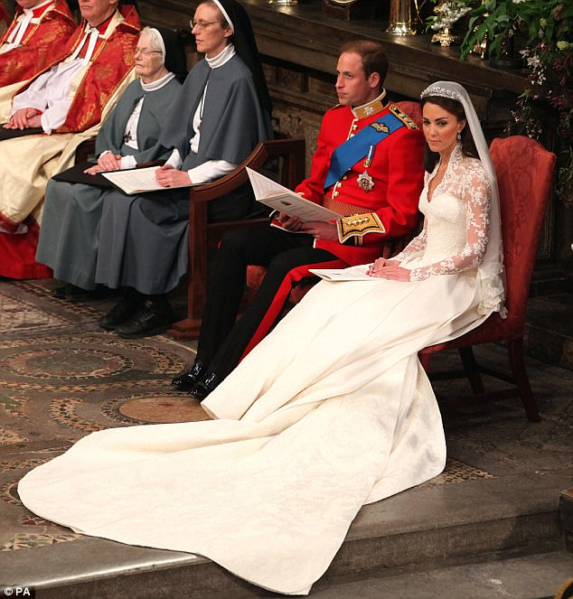 Prince William and Kate Middleton sit down during the service after he put the wedding band on her finger