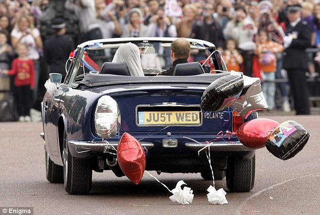 Happy couple: The Aston Martin Volante is decorated with balloons and a 'Just Wed' registration plate, as William and Catherine emerge in the soft-top vehicle