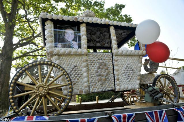 Kate Middleton's image looks out of a miniature horse-drawn carriage in her home village of Bucklebury, West Berkshire