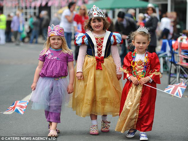 Fairytale: Three little princesses wander down the high street in Alcester, waving flags at one of the country's biggest street parties