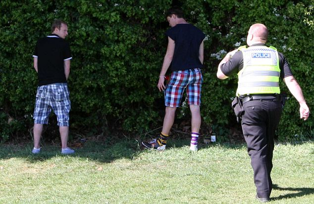 Bad behaviour: A policeman tells students to stop urinating into the bushes on Jesus Green in Cambridge