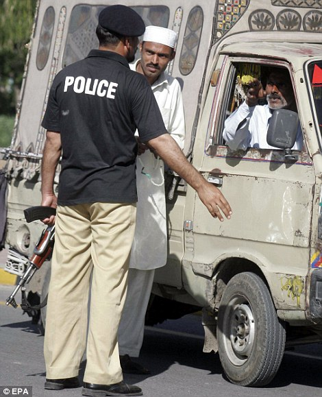 Pakistani police stop people as they secure the scene where according Bin Laden was killed