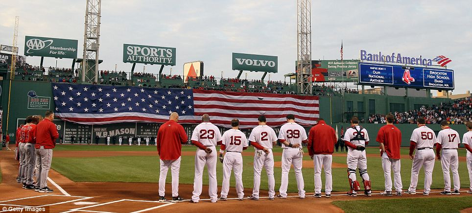 Players from the Boston Red Sox and the Los Angeles Angels watch as a giant American flag is unfurled before last night's game in Boston